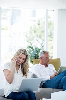 Mulher sorridente, falando no telefone pelo homem usando tablet
