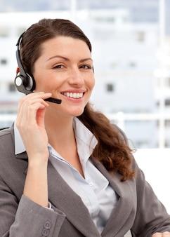 Mulher sorridente falando nos fones de ouvido