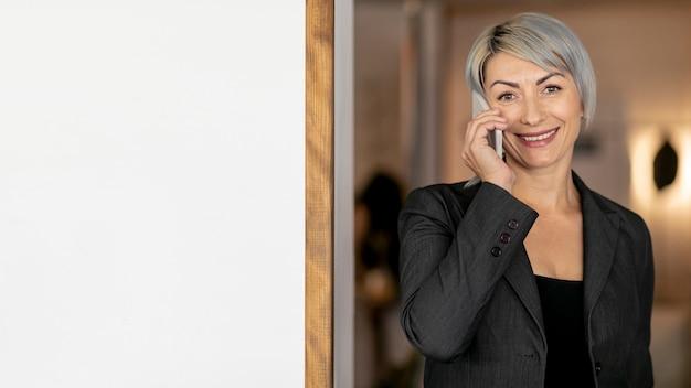 Mulher sorridente, falando sobre telefone cópia-espaço