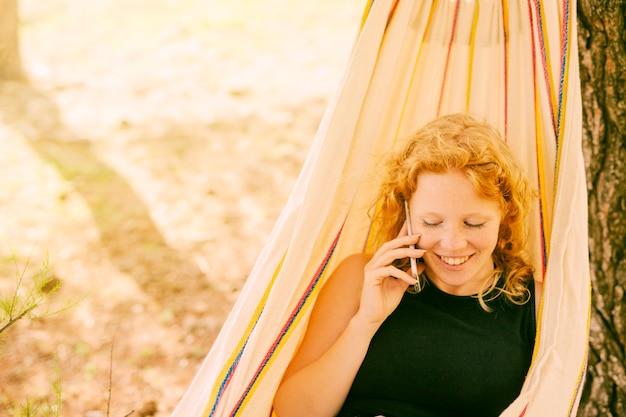 Mulher sorridente, falando, telefone, em, rede