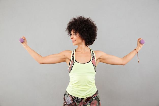 Mulher sorridente fazendo exercício com halteres e mostrando seu bíceps