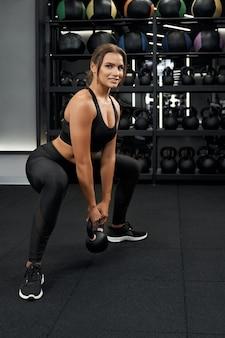 Mulher sorridente fazendo exercícios com kettlebells