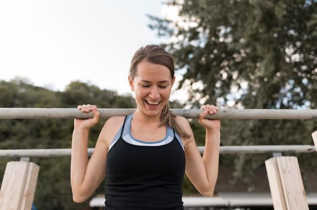 Mulher sorridente fazendo exercícios em roupas esportivas