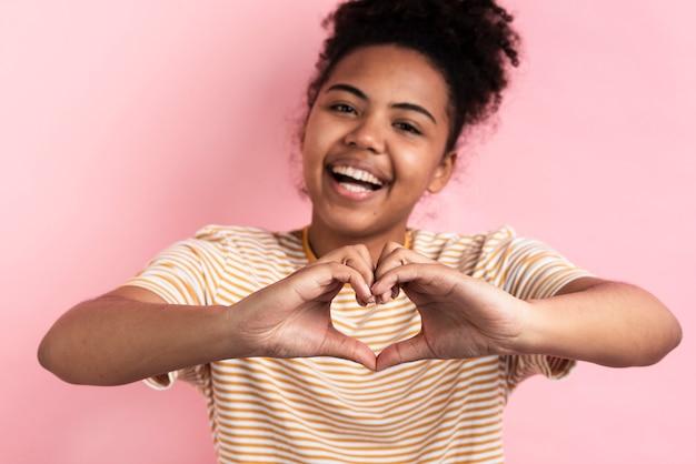 Mulher sorridente fazendo formato de coração com as mãos