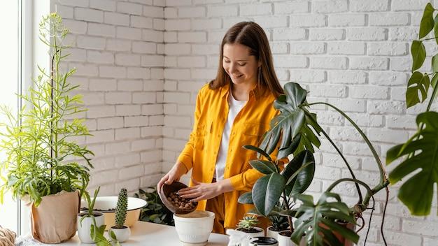 Mulher sorridente fazendo jardinagem em casa