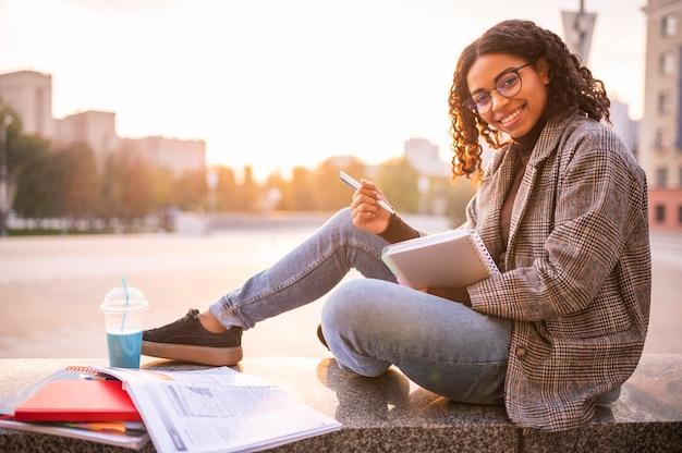 Mulher sorridente fazendo lição de casa ao ar livre