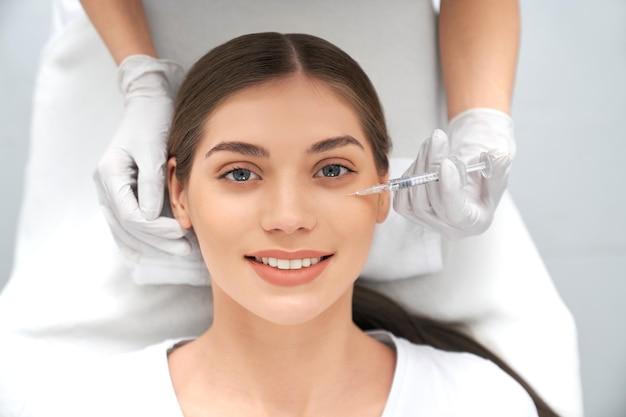 Mulher sorridente fazendo procedimento para esticar a pele