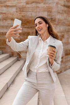 Mulher sorridente fazendo selfie com smartphone