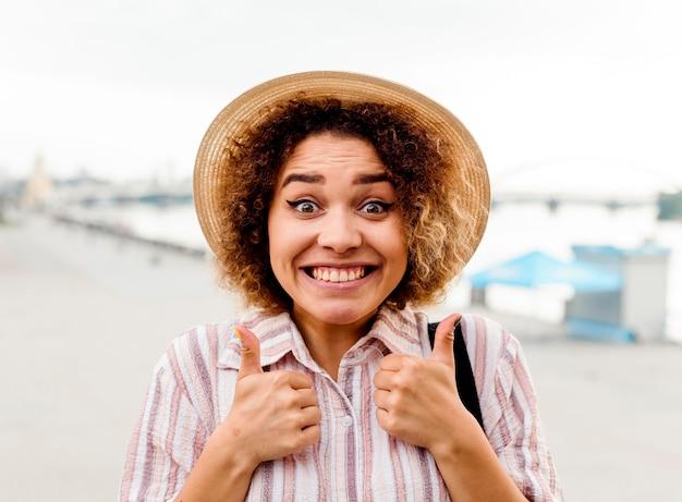 Mulher sorridente fazendo sinal de positivo