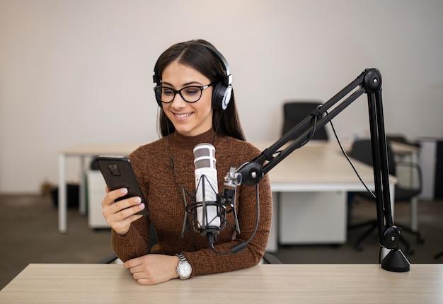Mulher sorridente fazendo um programa de rádio