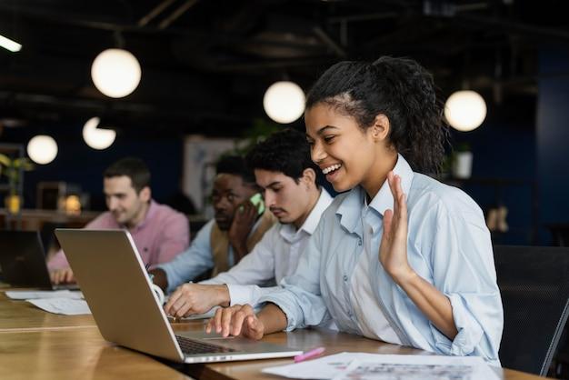 Mulher sorridente fazendo uma videochamada no escritório e acenando