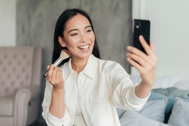 Mulher sorridente fazendo vlog com um pincel de maquiagem