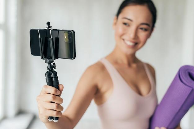 Mulher sorridente fazendo vlogs com seu telefone