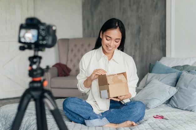 Mulher sorridente fazendo vlogs e olhando dentro de uma caixa