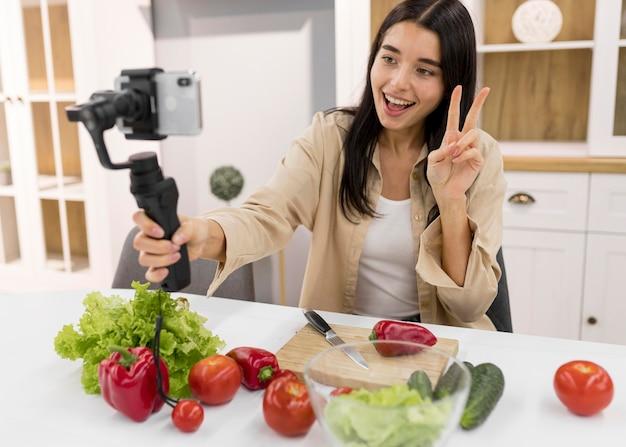 Mulher sorridente fazendo vlogs em casa com vegetais e smartphone