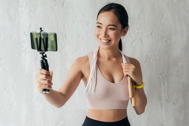 Mulher sorridente fazendo vlogs em roupas esportivas