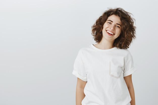 Mulher sorridente feliz amigável com cabelo encaracolado olhando