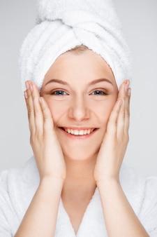 Mulher sorridente feliz aplicar creme facial, conceito de skincare