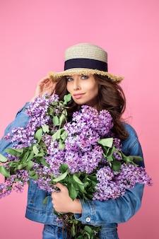 Mulher sorridente feliz, apreciando o cheiro de flores lilás buquê sobre