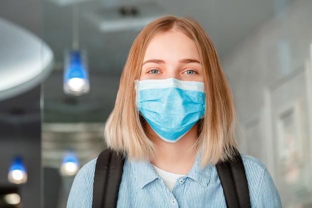 Mulher sorridente feliz colegial na máscara protetora azul com mochila. estudante de jovem mulher com máscara médica. retrato de estudante loira menina no interior da universidade durante o lockdow.