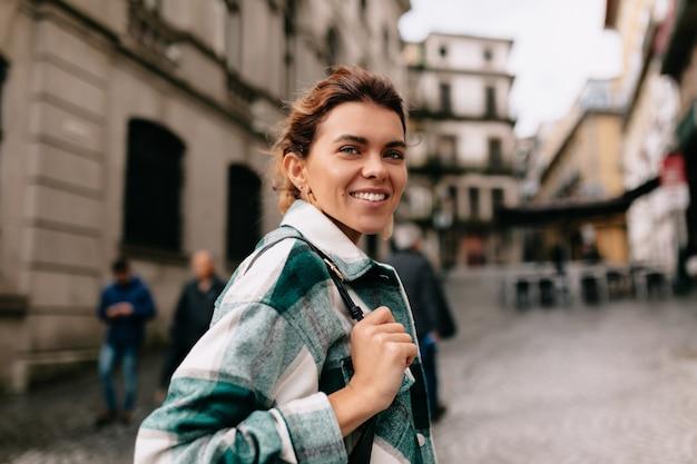 Mulher sorridente feliz com cabelo loiro, vestindo camisa listrada, andando na rua velha e ensolarada. uma jovem com bolsa está andando na cidade