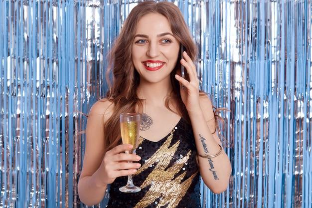 Mulher sorridente feliz com cachos, falando ao telefone com taça de champanhe nas mãos, tem lábios vermelhos, usando um vestido preto elegante, posando contra uma parede decorada com enfeites de prata.