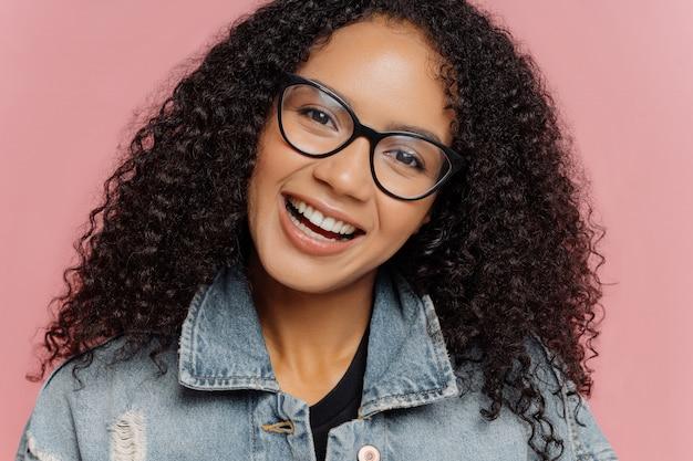Mulher sorridente feliz com penteado afro encaracolado escuro, inclina a cabeça, usa óculos ópticos e jaqueta jeans