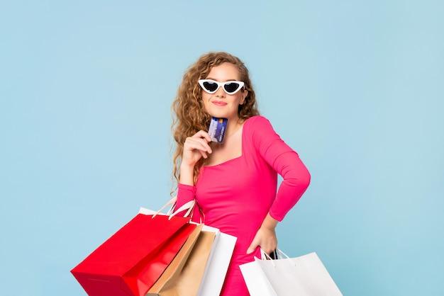Mulher sorridente feliz com sacos de compras, mostrando o cartão de crédito