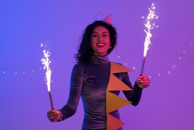 Mulher sorridente feliz comemorando com fogos de artifício. festa de ano novo.