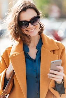 Mulher sorridente feliz de casaco e óculos de sol