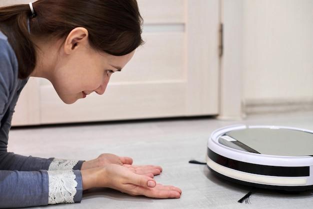 Mulher sorridente feliz deitada no chão e olhando para o aspirador de pó robótico. conhecendo um novo amigo robô e feliz com o dispositivo inteligente