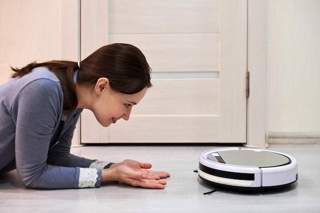 Mulher sorridente feliz deitada no chão e olhando para o aspirador de pó robótico.