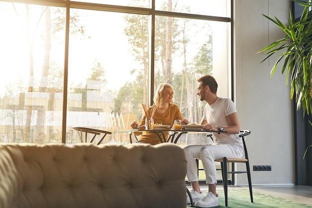 Mulher sorridente feliz e bonita e seu jovem marido alegre sentado à mesa na hora do almoço
