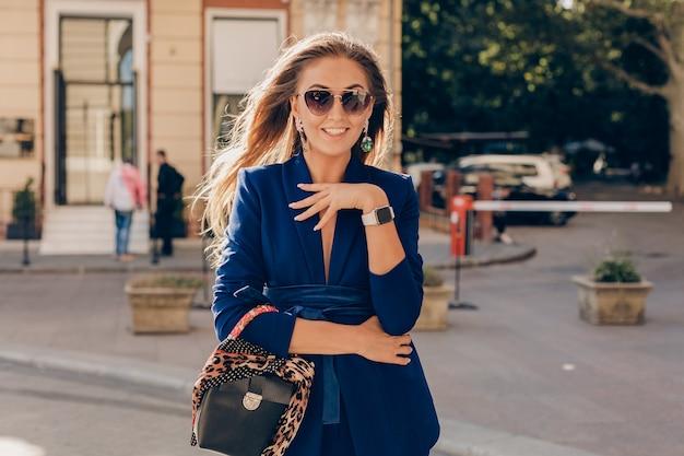 Mulher sorridente feliz e elegante em um terno elegante segurando uma bolsa da moda