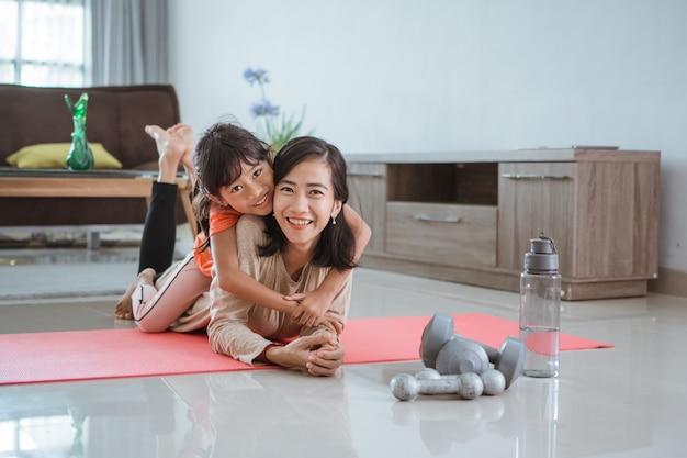 Mulher sorridente feliz e filha olhando para a câmera enquanto se exercitam juntas em casa