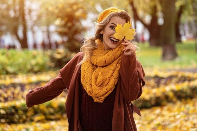 Mulher sorridente feliz esconde o olho com uma folha amarelada em uma boina de malha amarela com folhas de outono na mão e outono jardim ou parque amarelo