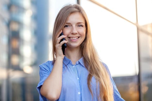 Mulher sorridente feliz falando no telefone celular e escritório oposto