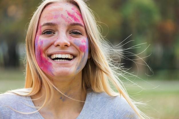 Mulher sorridente feliz mostra seu rosto colorido
