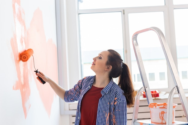 Mulher sorridente feliz pintando a parede interior da casa nova. conceito de redecoração, renovação, reparação e refresco de apartamentos.