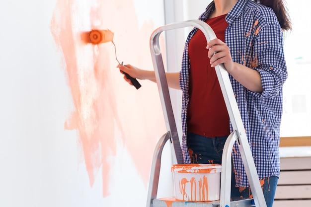 Mulher sorridente feliz pintando a parede interior da casa nova. redecoração, reforma, conserto de apartamentos