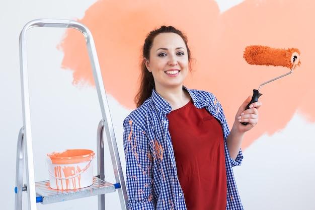 Mulher sorridente feliz pintando a parede interior da casa nova.