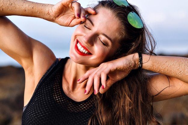 Mulher sorridente feliz positiva se divertindo e aproveitando o verão, close-up retrato, pele perfeita e maquiagem natural, conceito relaxante.