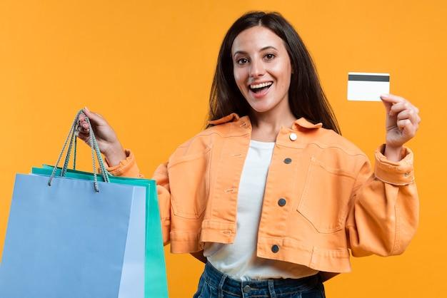 Mulher sorridente feliz segurando cartão de crédito e sacolas de compras