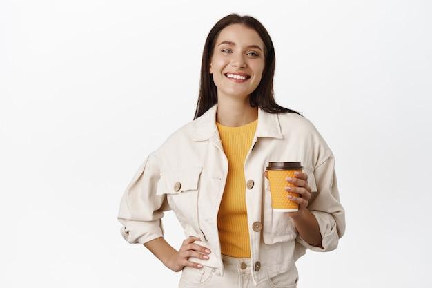 Mulher sorridente feliz tomando café do copo amarelo para viagem, comprando bebida no café e andando na cidade, satisfeito em pé no branco