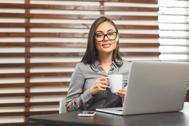 Mulher sorridente feliz trabalhando com laptop e bebendo café