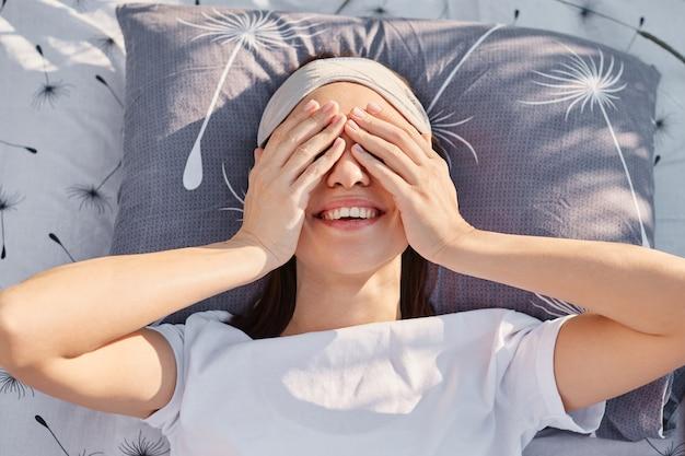 Mulher sorridente feliz vestindo camiseta branca casual deitada na cama ao ar livre, cobrindo os olhos com as palmas das mãos, acordando depois de dormir na natureza, expressando emoções positivas.