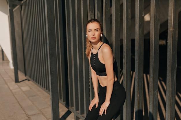 Mulher sorridente fitness em fones de ouvido malhando e correndo na praça do esporte