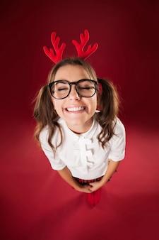 Mulher sorridente fofa com fita para a cabeça e chifres de rena