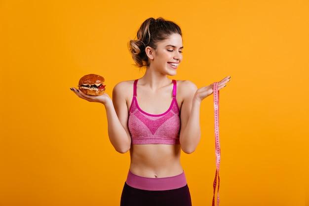 Mulher sorridente fofa posando com hambúrguer