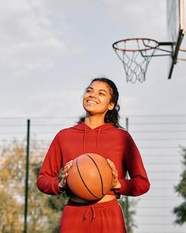 Mulher sorridente jogando basquete ao ar livre